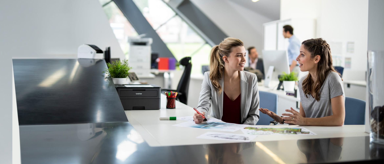 Dwie kobiety siedzą przy biurku w biurze i rozmawiają, w tle widać mężczyznę, drukarki, kubki, dokumenty