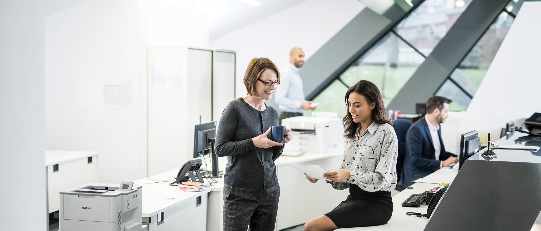 kobiety analizują dokumenty w biurze, drukarka brother w tle