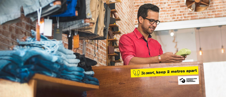 mężczyzna przyjmuje płatność w sklepie detalicznym
