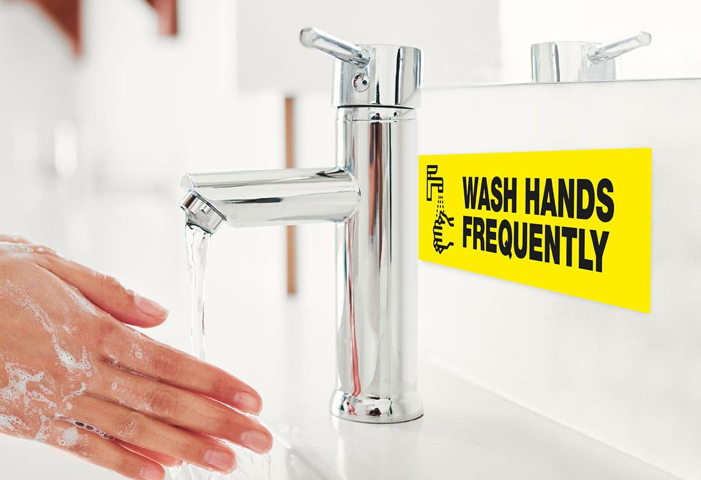 osoba myje ręce, obok widoczna jest etykieta z instrukcją