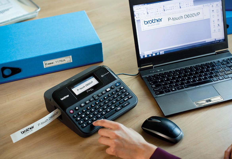 Drukarka etykiet P-touch stoi na biurku, jest podłączona do laptopa, drukuje etykietę
