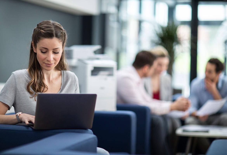 Kobieta siedzi na sofie i korzysta z laptopa, w tle znajdują się ludzie
