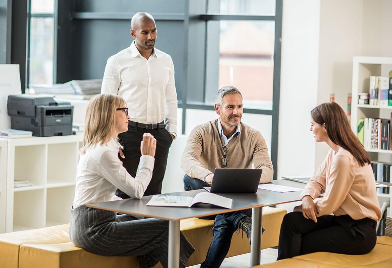 grupka osób w biurze rozmawia, w tle monochromatyczne urządzenie laserowe