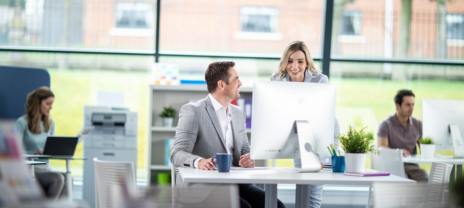 Mężczyzna siedzi przy biurku i rozmawia z kobietą z dlugimi blond włosami, w tle widać pracujących ludzi na laptopach, drukarki, kubki, rośliny, krzesła itp