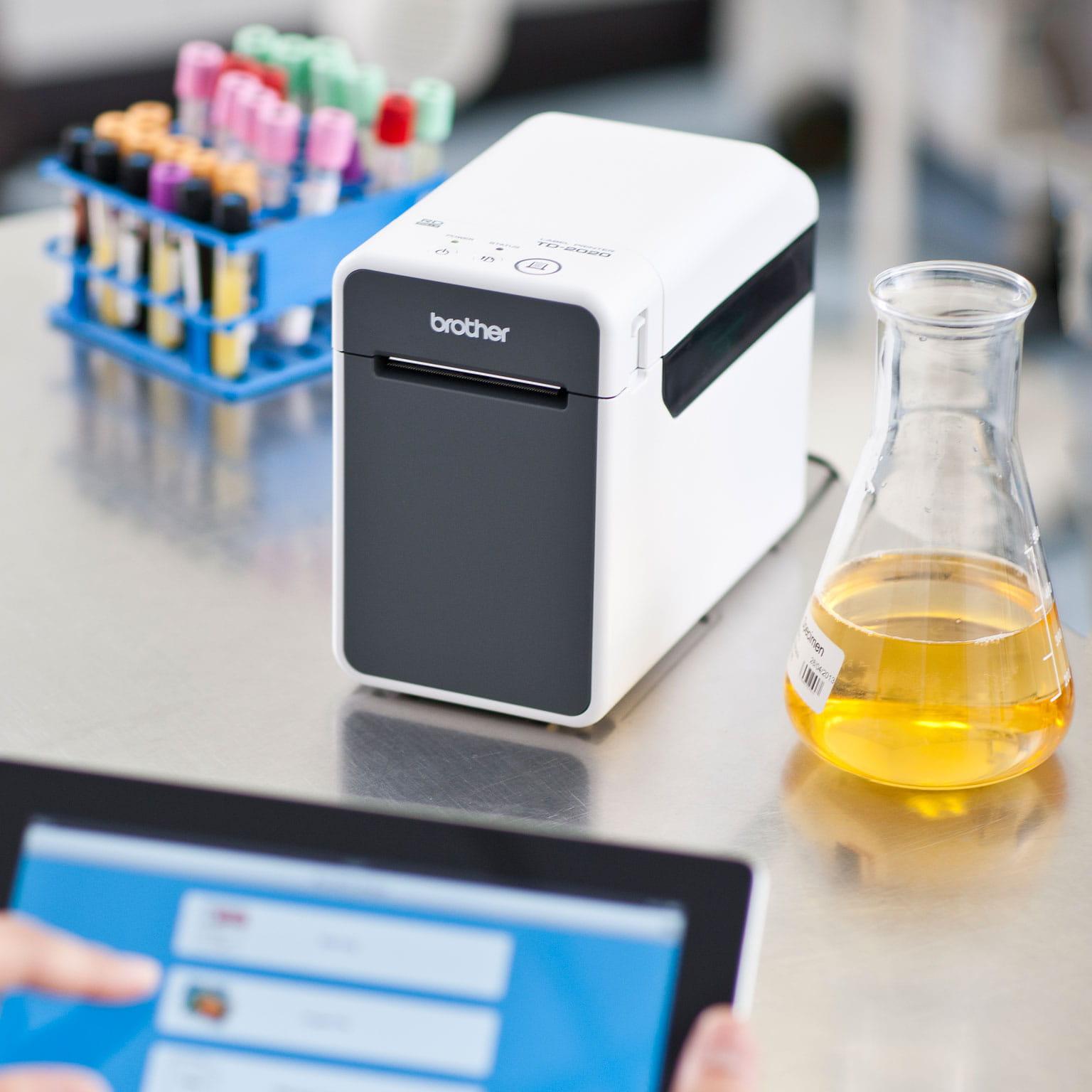 Lekarz drukuje etykiety testowe do probówek przy użyciu drukarki firmy Brother