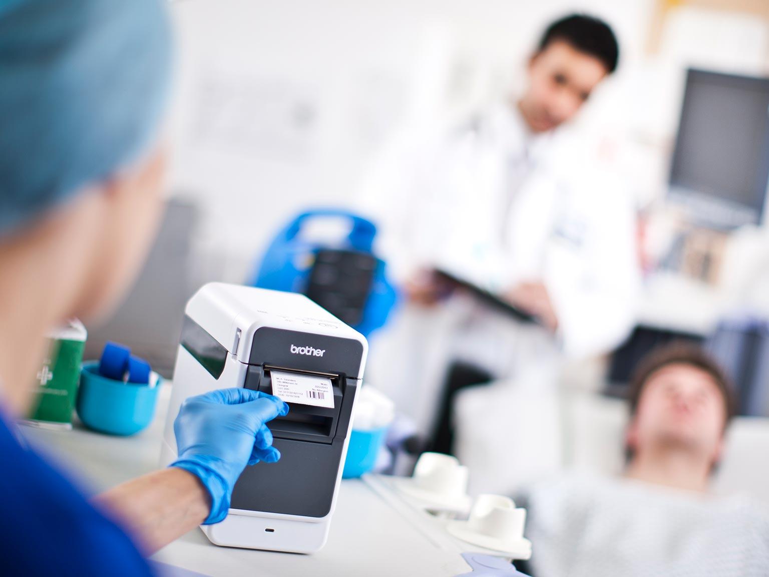 seria drukarek etykiet Brother TD2 w środowisku medycznym, pielęgniarka odbiera wydrukowaną etykietę