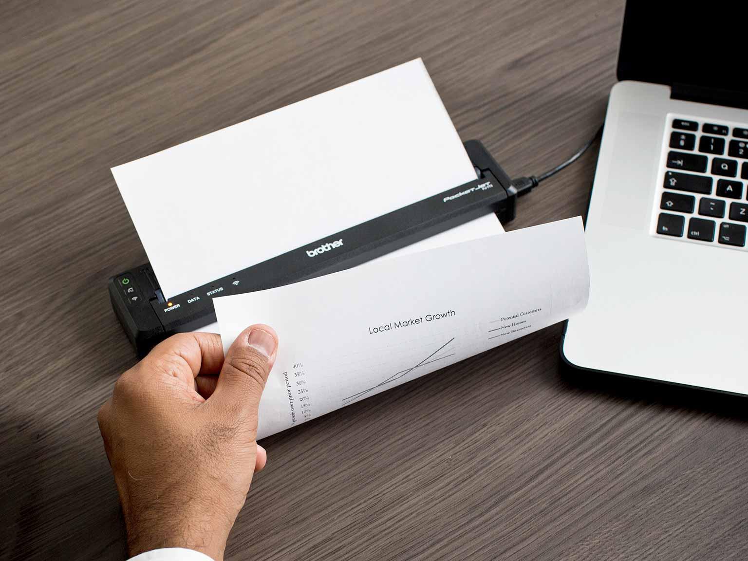 handlowiec drukuje dokument A4 na przenośnej drukarce Brother PJ