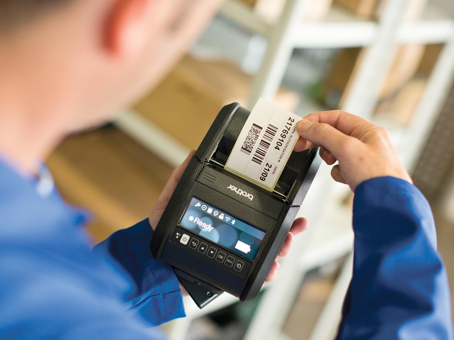 pracownik magazynowy trzyma drukarkę z serii RJ w ręku, w tym czasie etykieta jest drukowana