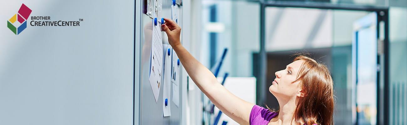 kobieta przyczepina notatki w biurze do tablicy