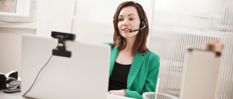 Kobieta w biurze rozmawiająca przez zestaw mikrofonowo-słuchawkowy