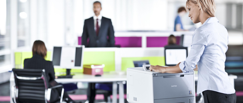 Kobieta obsługująca drukarkę Brother w otoczeniu biurowym