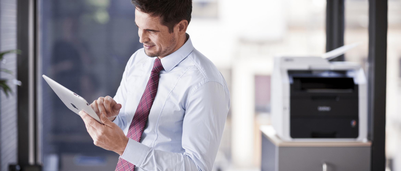 Mężczyzna w otoczeniu biurowym pracujący na iPadzie