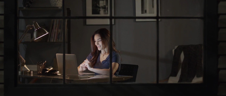 Kobieta siedziąca wieczorem przy biurku z laptopem