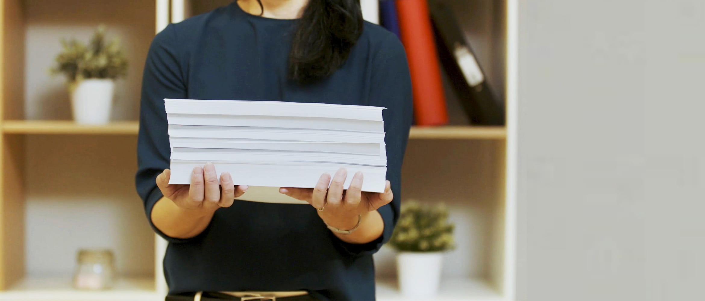Kobieta trzyma stos papieru