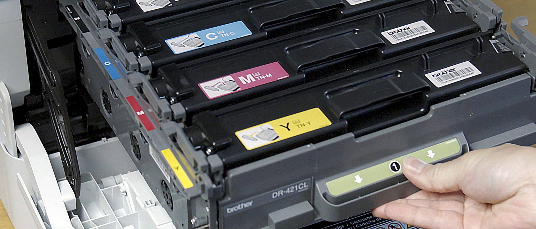 Osoba otwiera drukarkę i wyciąga kasety z tonerami