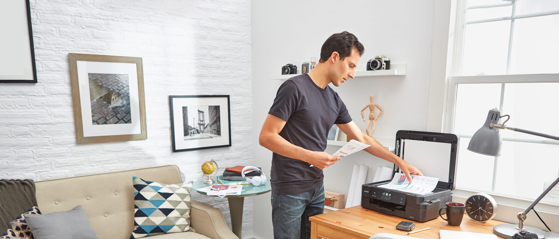 mężczyzna skanuje dokumenty w domu korzystając z urządzenia Brother