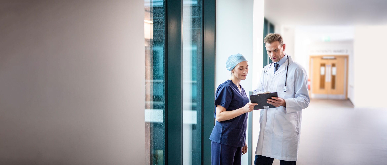 Doktor w białym fartuchu i z stetoskopem rozmawia z panią doktor na szpitalnym korytarzu