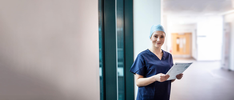 Pani chirurg trzyma niebieski folder, stoi na korytarzu w szpitalu