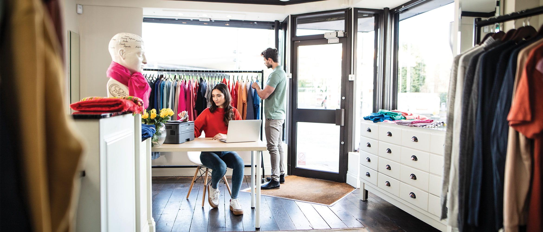 Mężczyzna kupuje ubrania w sklepie z odzieżą, kobieta siedzi przy biurku i drukuje dokumenty