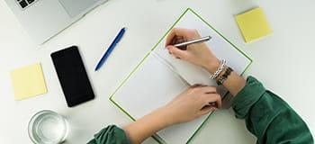 kobieta robi notatki w notatniku, obok leży telefon