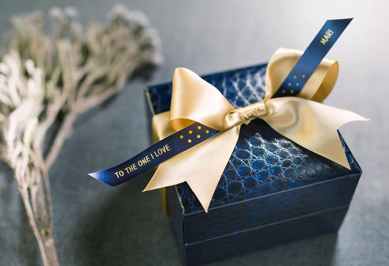 Pudełko na prezent owinięte złotą wstążką i granatowa satynowa taśma wstążkowa Brother ze złotym nadrukiem