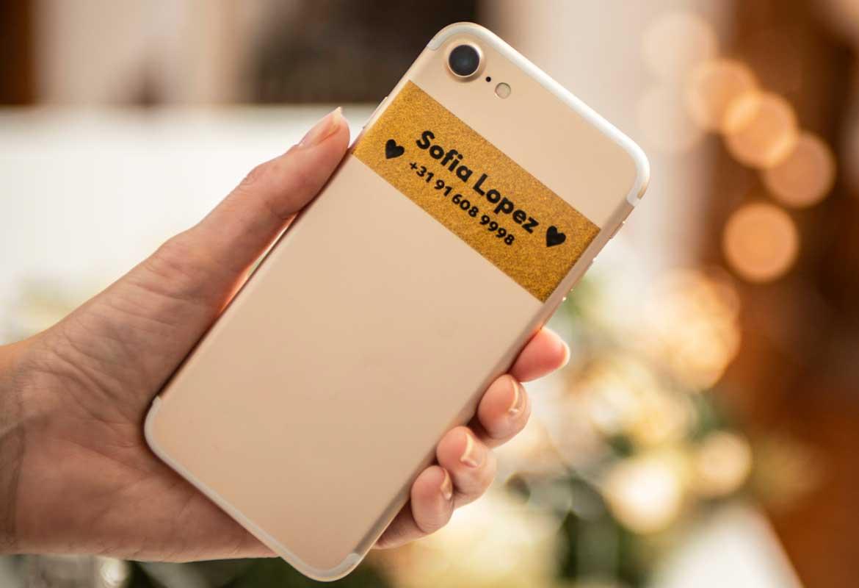 Etykieta premium na smartfonie z czarnym nadrukiem na złotym brokatowym tle przedstawiająca: imię, nazwisko oraz numer kontaktowy właściciela