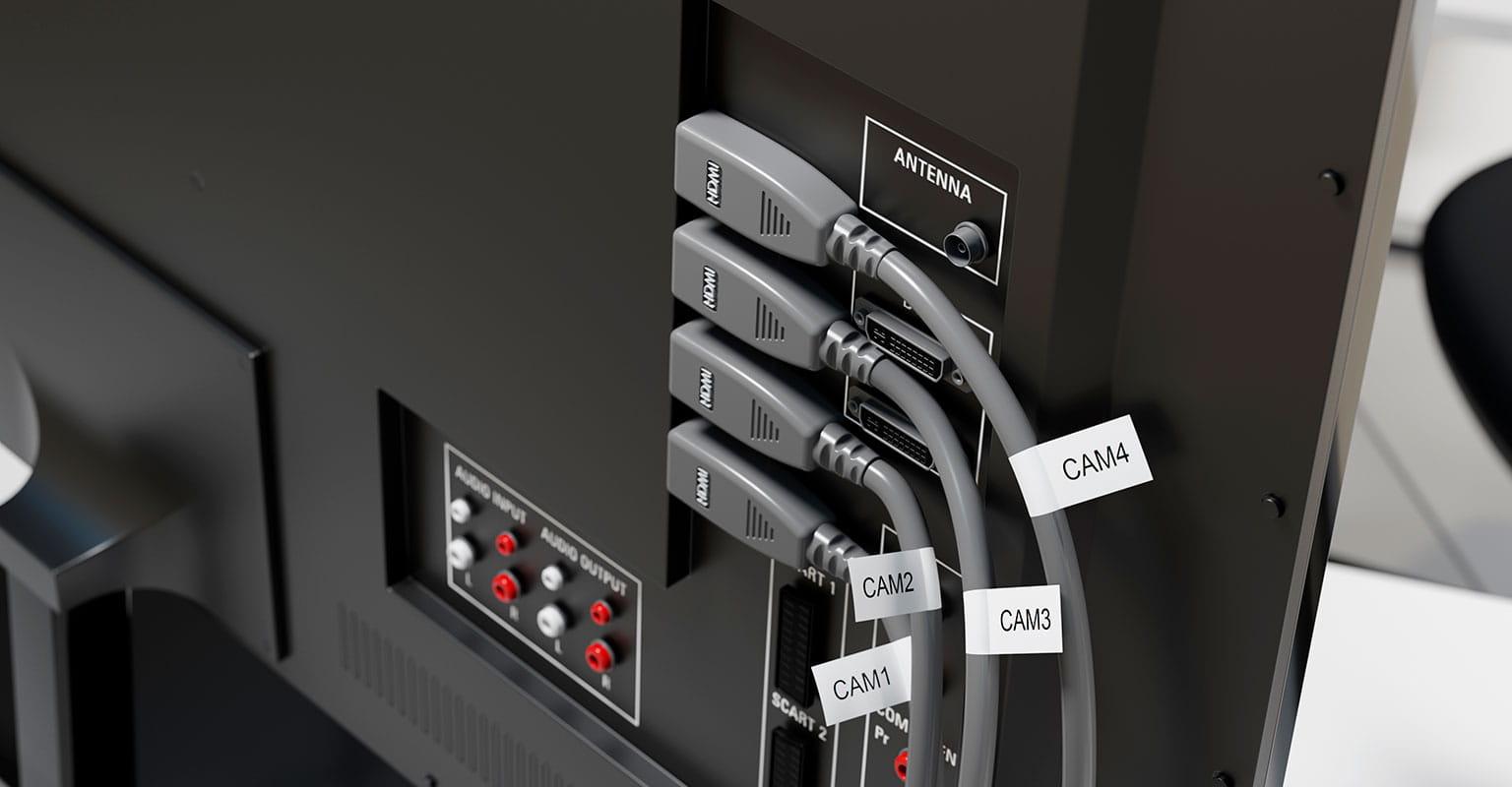 Etykiety Brother z elastycznym identyfikatorem owinięte wokół kabli wideo HDMI wchodzących do monitora
