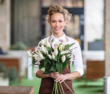 Kobieta z kręconymi włosami w brązowym fartuchu z dużą wiązką kwiatów