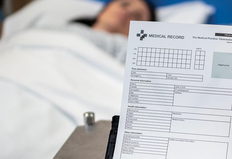 Pacjentka leży w łóżku, a model Brother ADS-3600W skanuje jej dokumentację medyczną