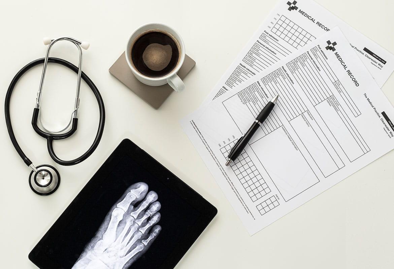 Formularze medyczne, długopis, filiżanka kawy na spodeczku, stetoskop, prześwietlenie stopy
