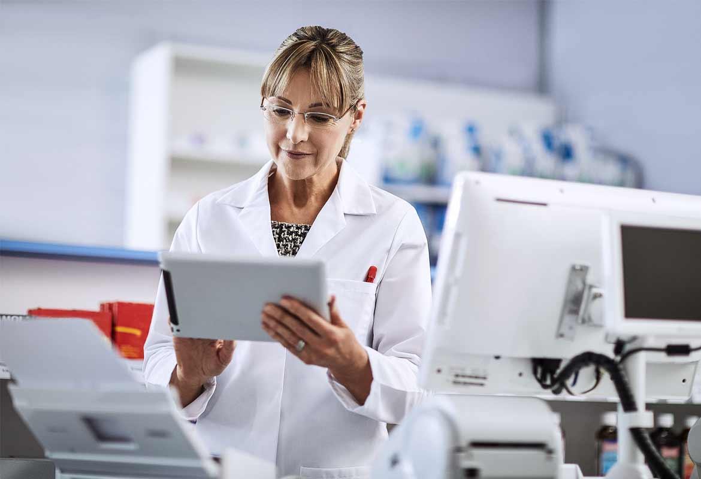 Farmaceuta w białym fartuchu sprawdza dane na tablecie