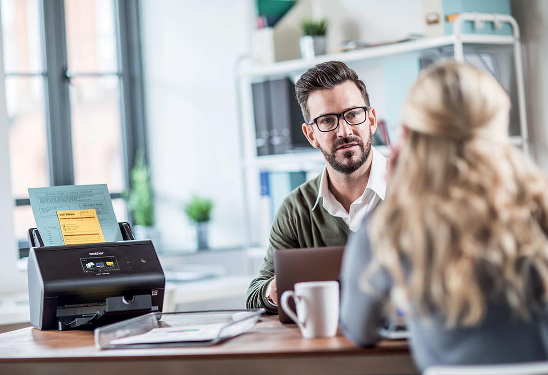 Mężczyzna w okularach i swetrze siedzi przy biurku, obok skaner Brother, klientka z długimi blond włosami siedzi po przeciwnej stronie
