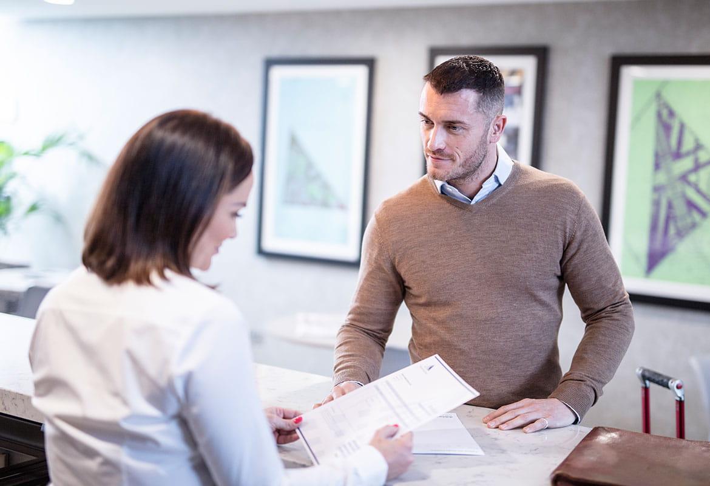 Kobieta z brązowymi włosami w białej koszuli trzyma dokument, stoi za biurkiem, obsługuje klienta, mężczyzna ubrany w brązowy sweter