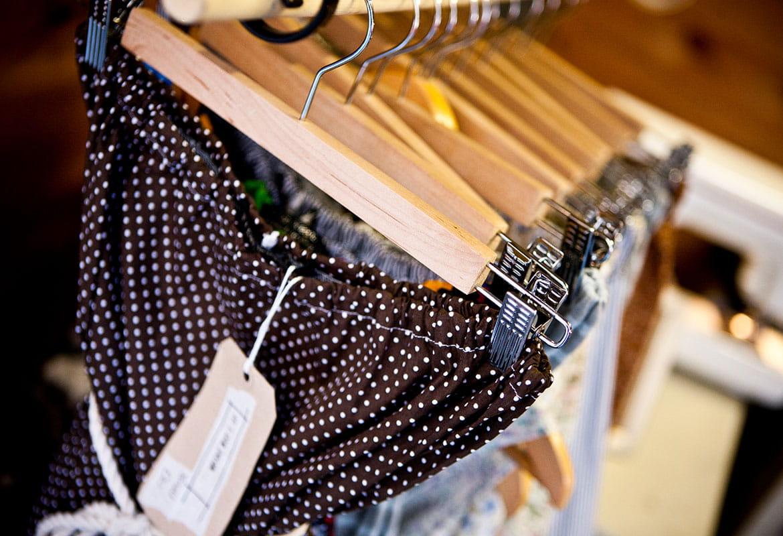 Niebieskie cętkowane spodnie, niebieskie topy zawieszone na drewnianych wieszakach z metką cenową