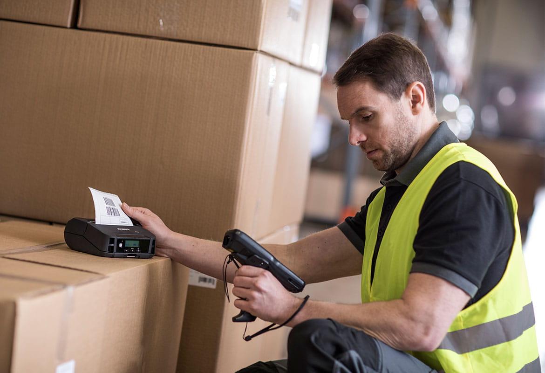 Mężczyzna w odblaskowej kamizelce skanuje kod kreskowy przy użyciu drukarki etykiet Brother, drukarka stoi na pudełku w magazynie