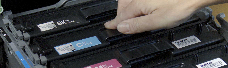 Osoba wkłada tonery do otwartej drukarki