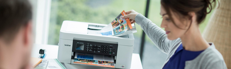 Kobieta siedzi przy biurku i odbiera dokumenty z drukarki