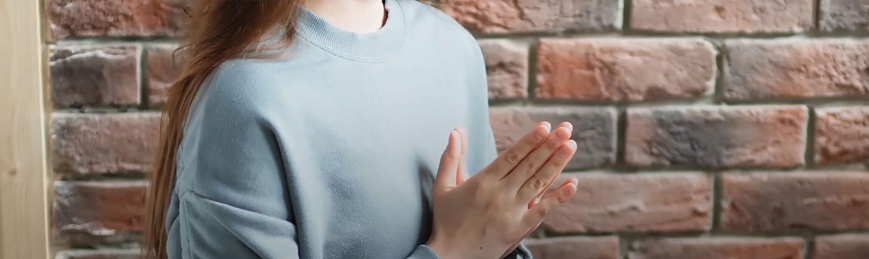 Siedząca kobieta z złączonymi dłońmi