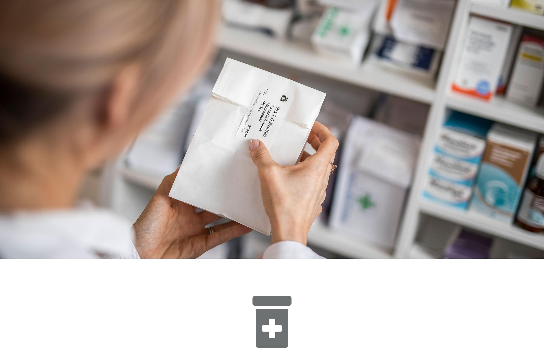 Farmaceutka etykietuje leki w aptece