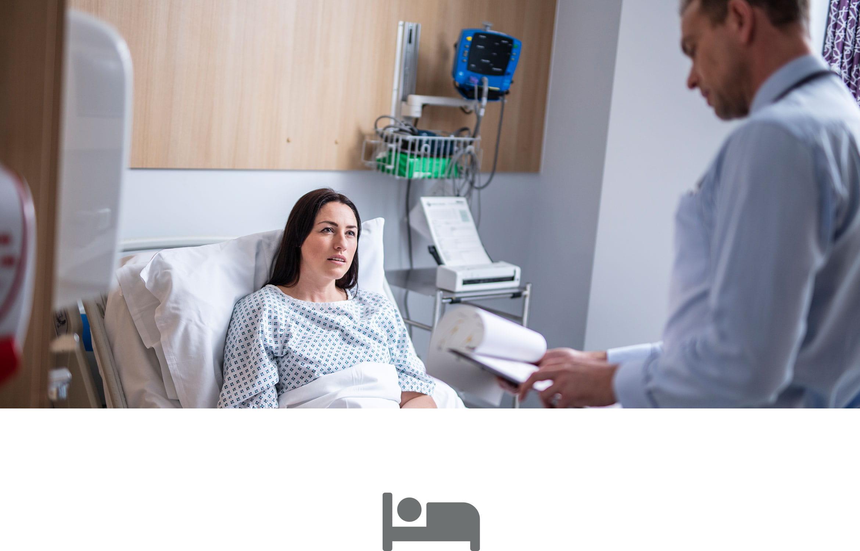 Pacjentka leży w łóżku szpitalnym, lekarz ogląda jej kartotekę, szara ikonka łóżka