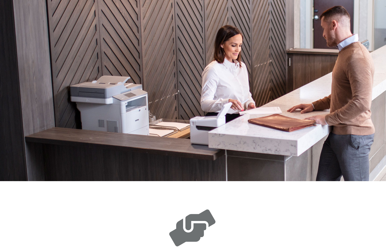 Klient otrzymuje pomoc od obsługi klienta, w tle drukarka laserowa, przy kasie stoi drukarka etykiet