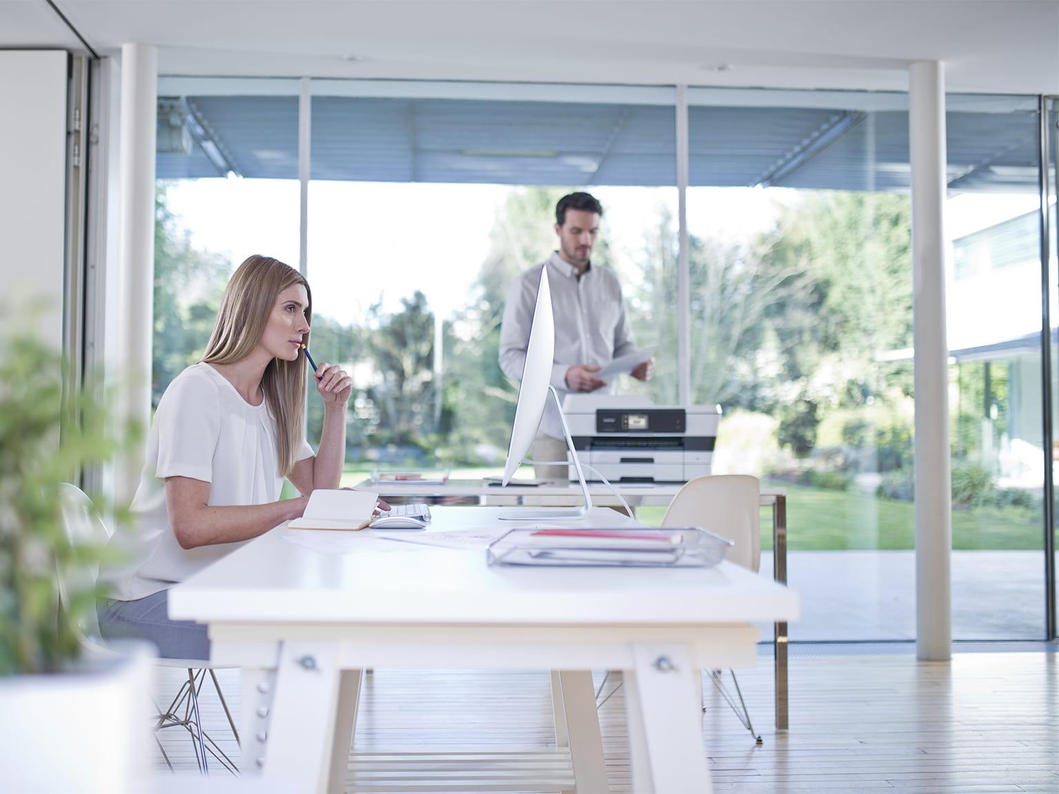Kobieta i mężczyzna w biurze z urządzeniem Brother