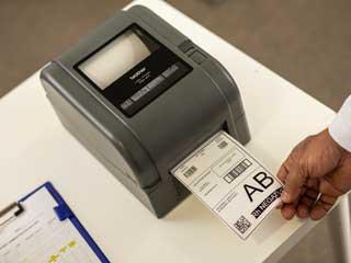 Etykieta drukowana przy pomocy stojącej na biurku drukarki Brother z serii TD-4D.
