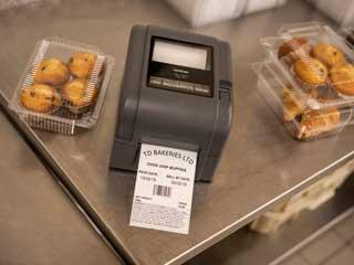 Drukarka etykiet Brother TD-4D drukuje etykietę stojąc na metalowym blacie w towarzystwie ciastek