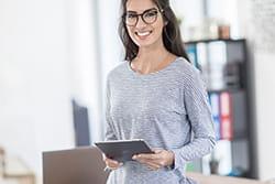 Kobieta trzyma w ręku tablet, na którym projetkutuje etykietę dzięki AirPrint i drukarkce VC-500W