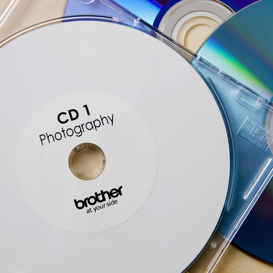 Oryginalne etykiety na rolce do płyt CD/DVD firmy Brother DK-11207  – czarny nadruk na białym tle, 58mm szerokości 2