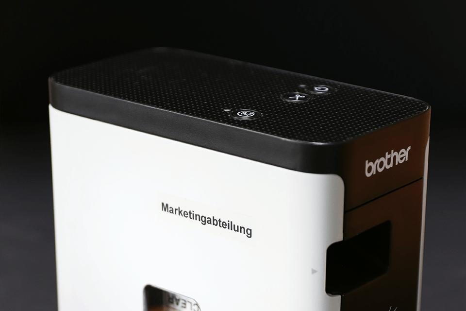 Oryginalna laminowana taśma z mocnym klejem TZe-S121 firmy Brother – czarny nadruk na przezroczystym tle, 9mm szerokości 4